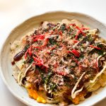Okonomiyaki is the famous Japanese savory pancake that is usually cooked at the dining table so you can customize it to your taste.