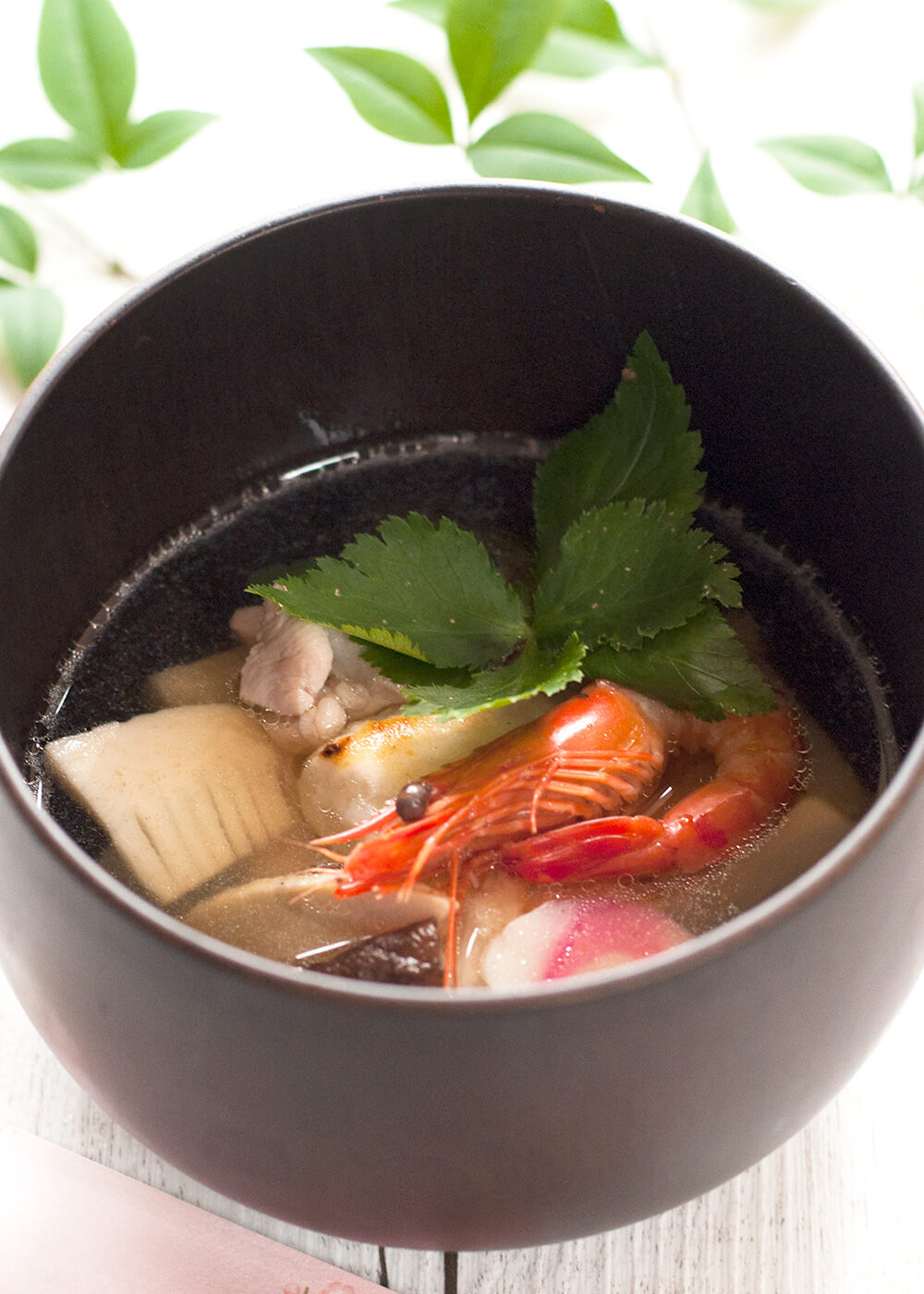 Ozoni is a special dish that most Japanese households serve on New Year's Day. It is a clear soup with cooked rice cakes and colourful ingredients such as prawns, shiitake, and mitsuba (wild Japanese parsley). Ingredients can vary and you can even make it vegetarian.