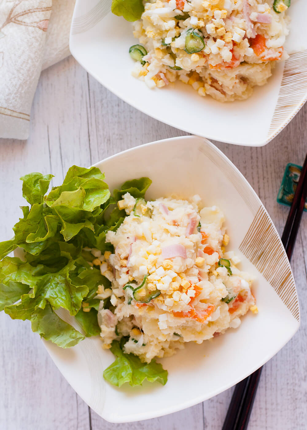 Japanese potato salad is like semi-mashed potatoesmixed withvegetables, ham, egg and mayonnaise. Small pieces of carrots, cucumbers, onions, ham and eggs make it visually appealing. It is not too creamy, not too rich,but flavoursome. What makes this potato salad stand out is the mushy texture and the famous Japanese mayonnaise, Kewpie mayonnaise.