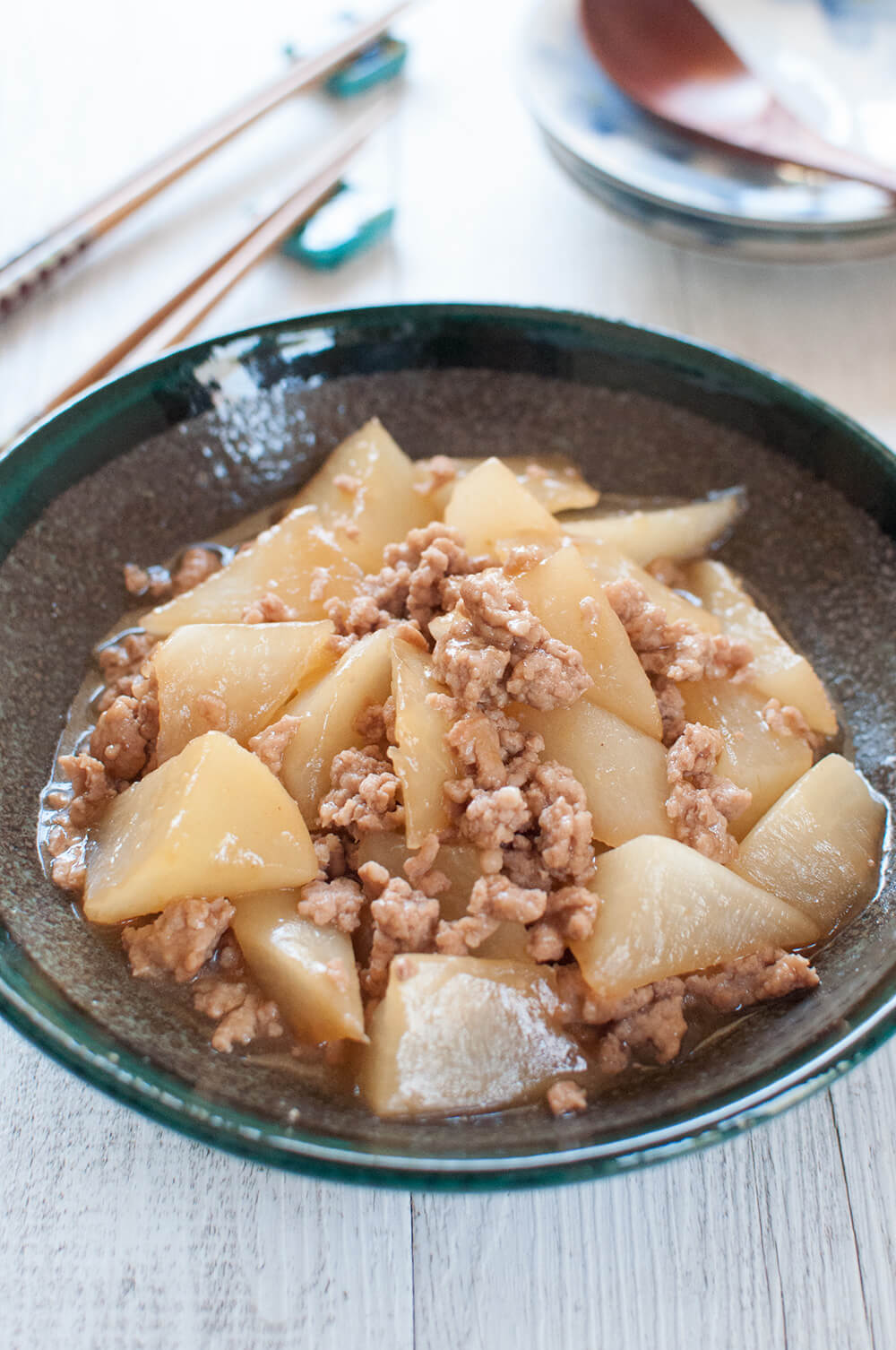 A simple braised white radish (daikon) becomes a surprisingly tasty dish when cooked in a thick soy flavoured sauce with pork mince (ground pork). The daikon is cooked until it becomes semi-transparent and tender. The meat sauce has a typical Japanese flavour with dashi, soy sauce, sake, mirin and sugar.