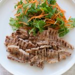 Pork Kasuzuke cooked on a griddle pan look appertaining with burnt lines. Served with mizuna and carrot salad.