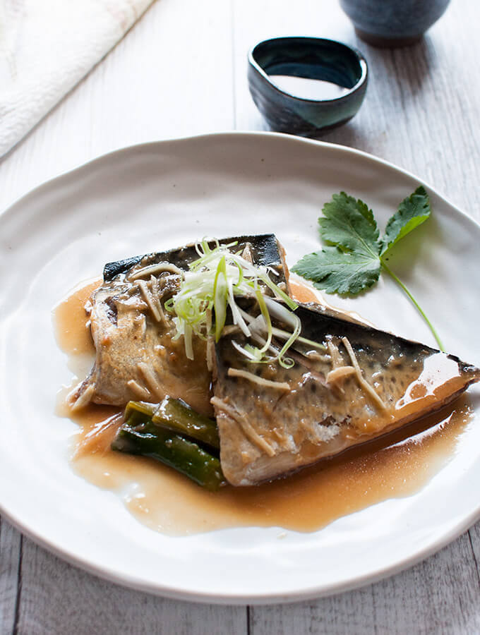 Simmered mackerel in miso served on a plate topped with julienned shallots (scallions)