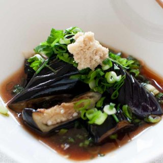 Deep Fried Eggplants (Agedashi Nasu) in dashi sauce topped with shallots and grated ginger.