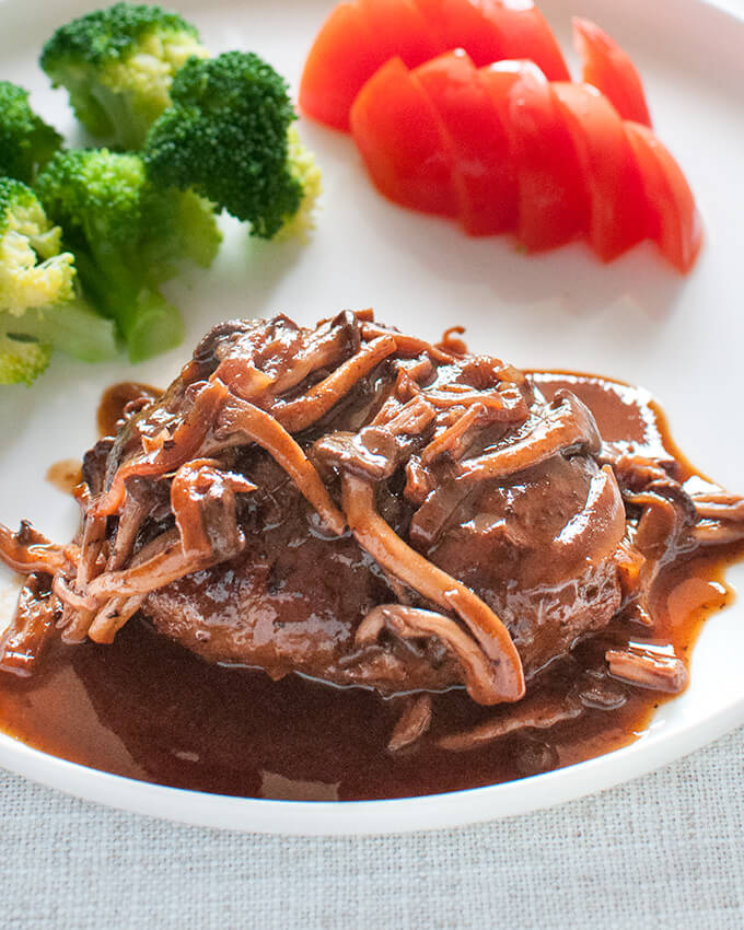 Stewed Hamburg Steak (Nikomi Hamburg) with Shimeji Mushroom Sauce. Great colour on the plate with broccoli and tomato on the side.