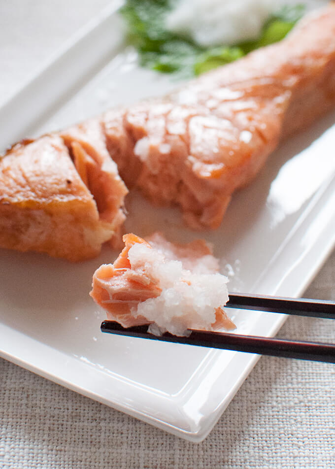 Zoomed in image of grilled salted salmon piece picked up with chopsticks.