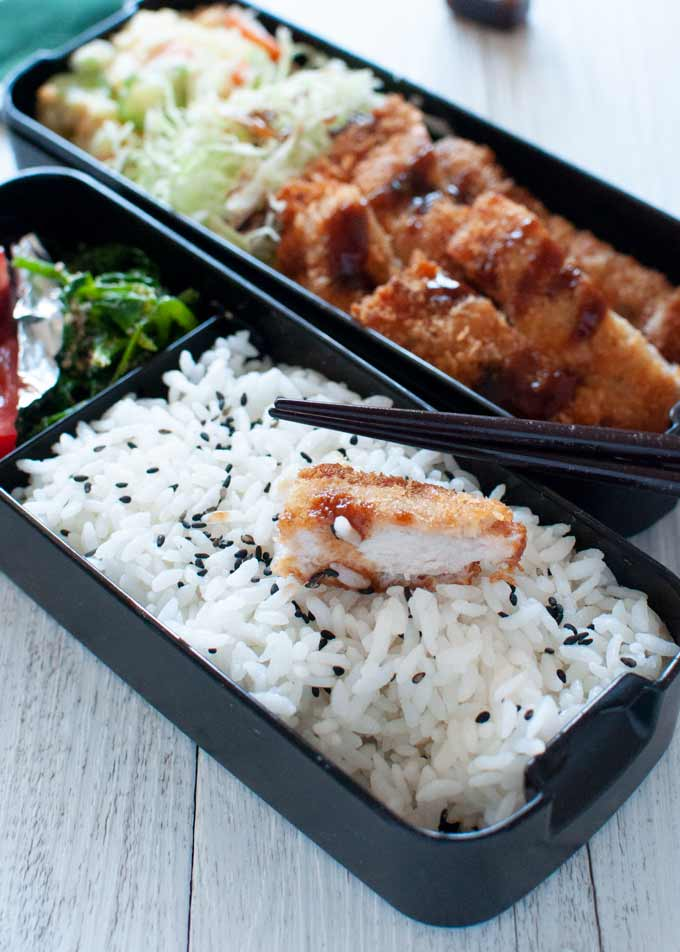 Tonkatsu Bento with a piece of half bitten tonkatsu on the rice.