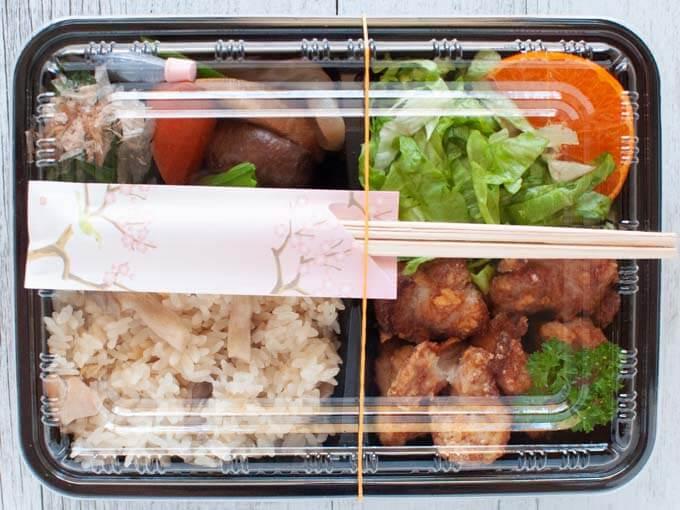 Karaage Bento box with a lid and chopsticks.