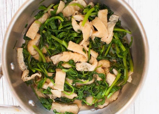 Snow pea leaves and aburrage cooked in a pot.