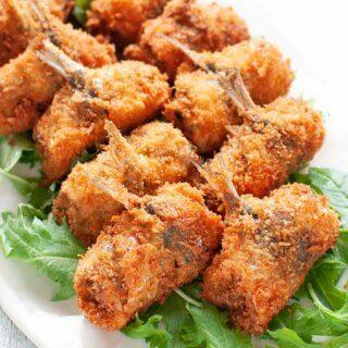 Deep fried stuffed sardines served on green salad leaves.