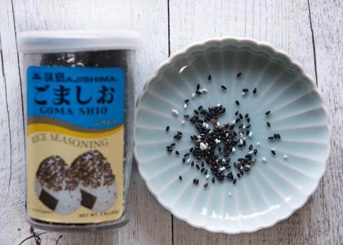 Gomashio - roasted sesame and salt in a container and on a plate.