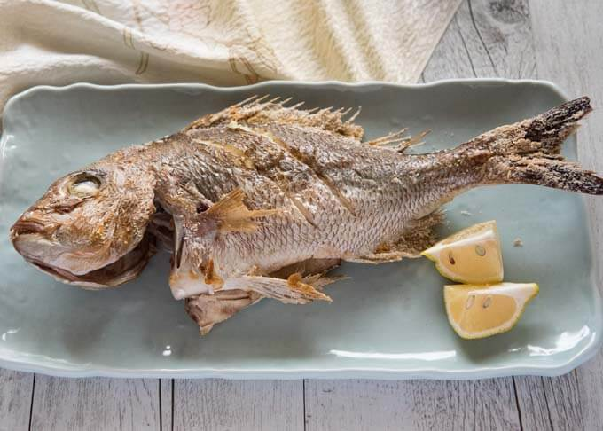 Grilled Whole Snapper served on. plate.