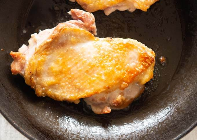 Browned chicken in frying pan.