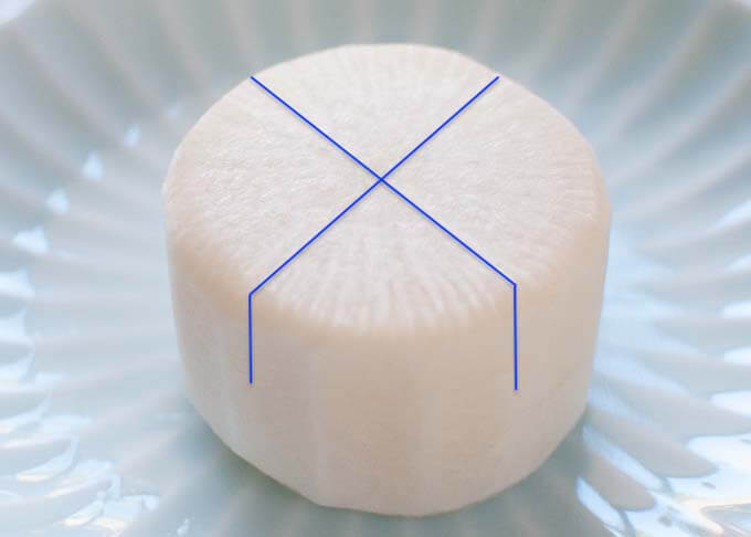 Photo of a daikon with the lines indicating where to make cuts to do Kakushibōchoō.