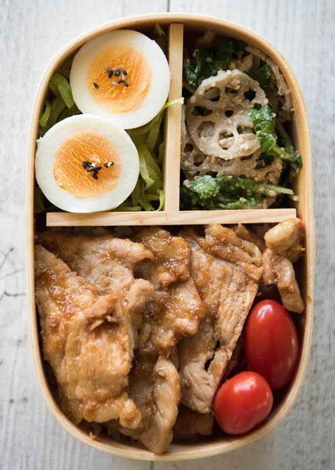 Top-down photo of Pork Shōgayaki Bento which contains Pork Shōgayaki, small tomatoes, boiled eggs on shredded lettuce and Lotus Root and Spinach salad.