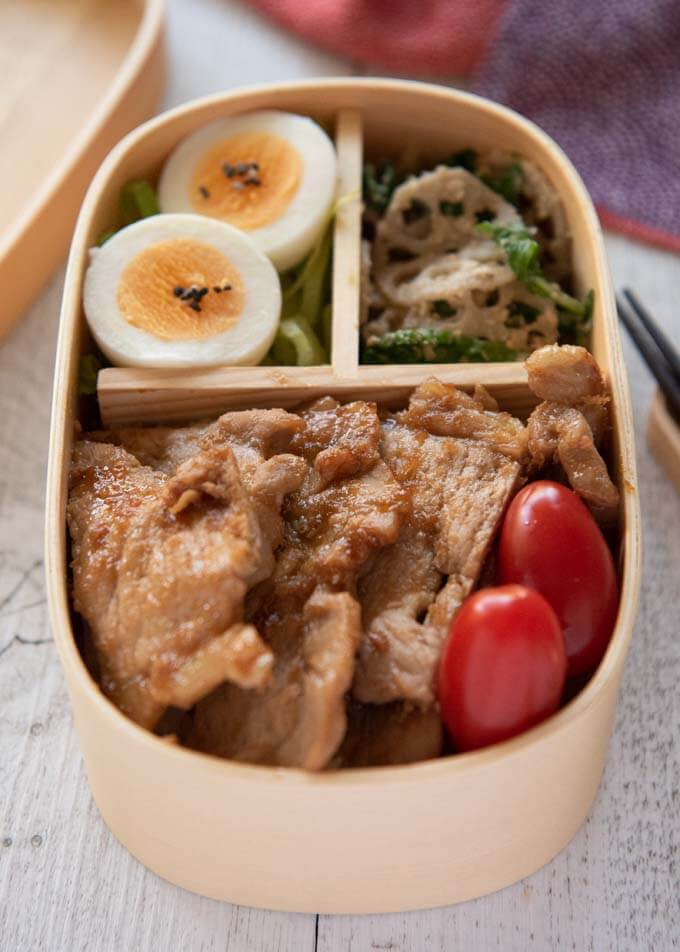 Photo of Pork Shōgayaki Bento which contains Pork Shōgayaki, small tomatoes, boiled eggs on shredded lettuce and Lotus Root and Spinach salad.