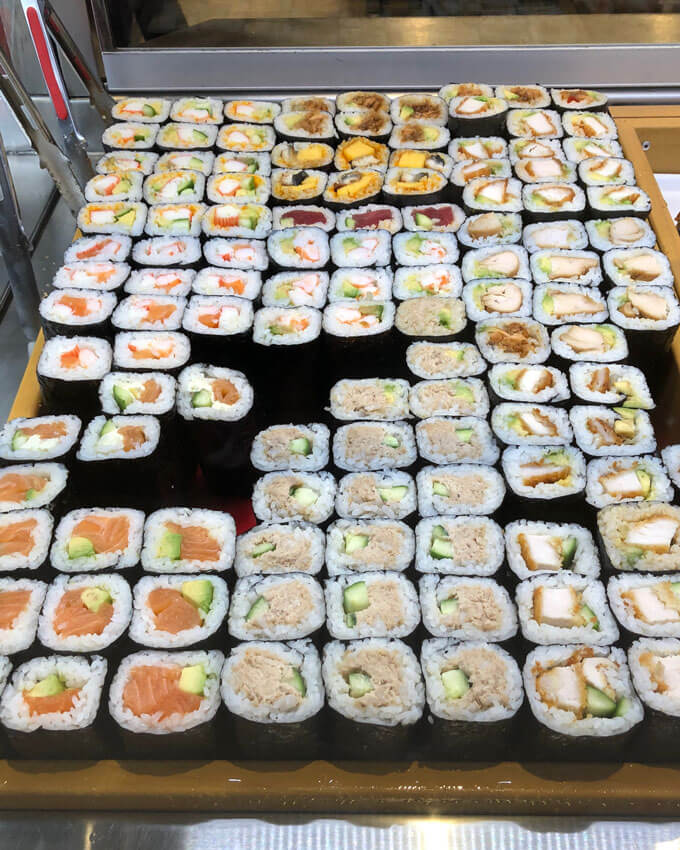 Different kinds of sushi rolls sold at a take away sushi shop.