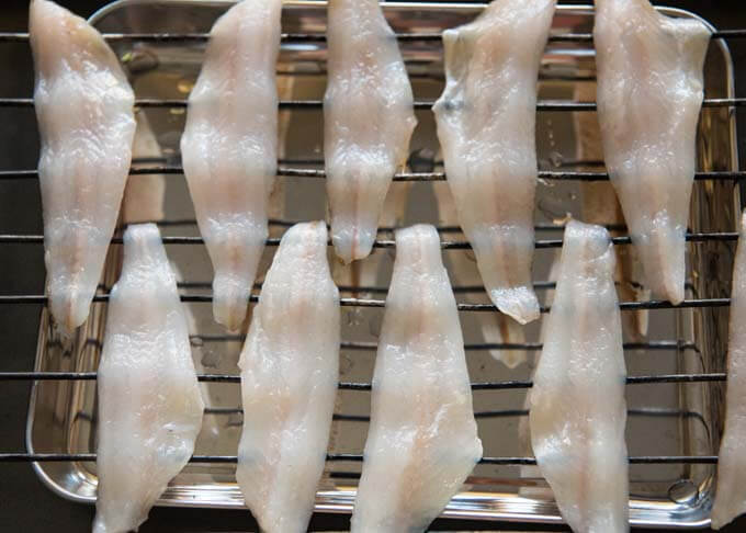 Fresh whiting fillets on a rack.