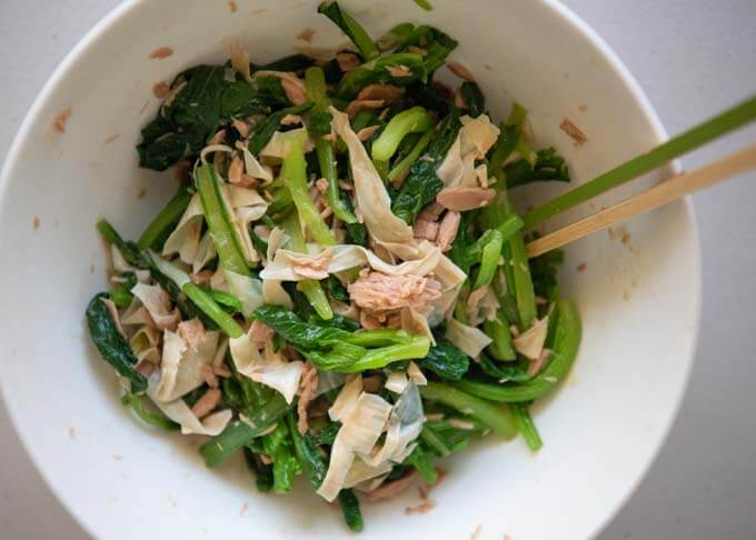Baby mustard greens, tuna and tofu skin pieces mixed in a mixing bowl.