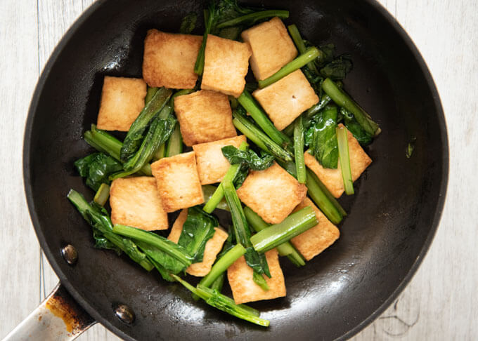 Stir-frying Choy Sum and Deep Fried thick Tofu.