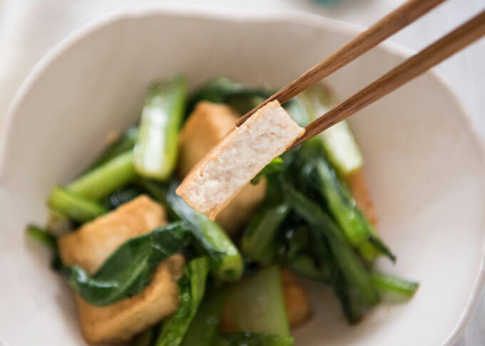 Showing the inside of deep fried tofu in stir-fry.