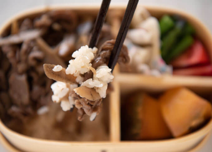 Zoomed-in photo of rpicking up the rice with beef with chopsticks.