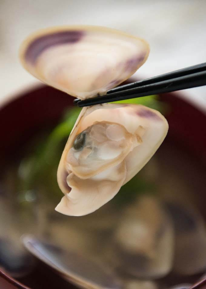 Photo of a clam picked up with chopsticks.
