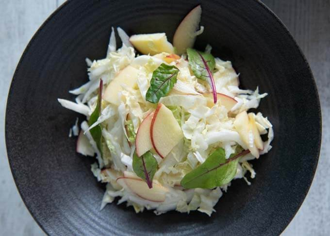Top-down photo of Chinese Cabbage and Apple Salad on a serving bowl.