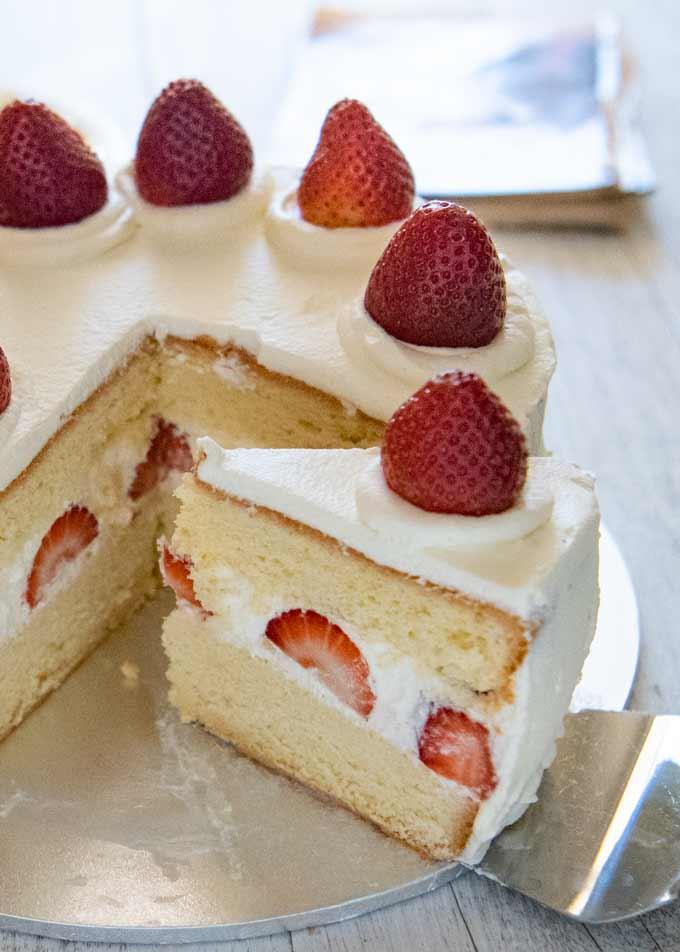 Hero shot of Japanese Strawberry Sponge Cake (Strawberry Shortcake), removing a slice..